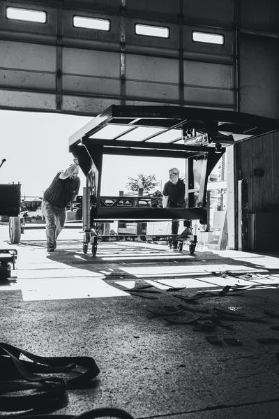 Two Keystone RV manufacturing team members rolling a fifth wheel RV chassis into the plant.