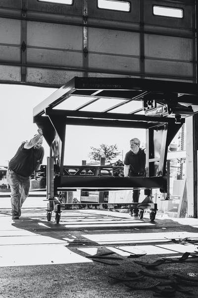 Two men rolling a fifth wheel chassis into a Keystone RV manufacturing plant.