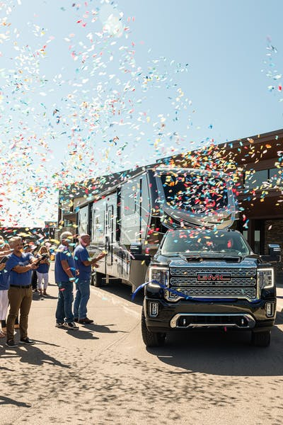 Keystone empolyees throwing confetti as the one millionth RV produced pulls away from the corporate headquarters.