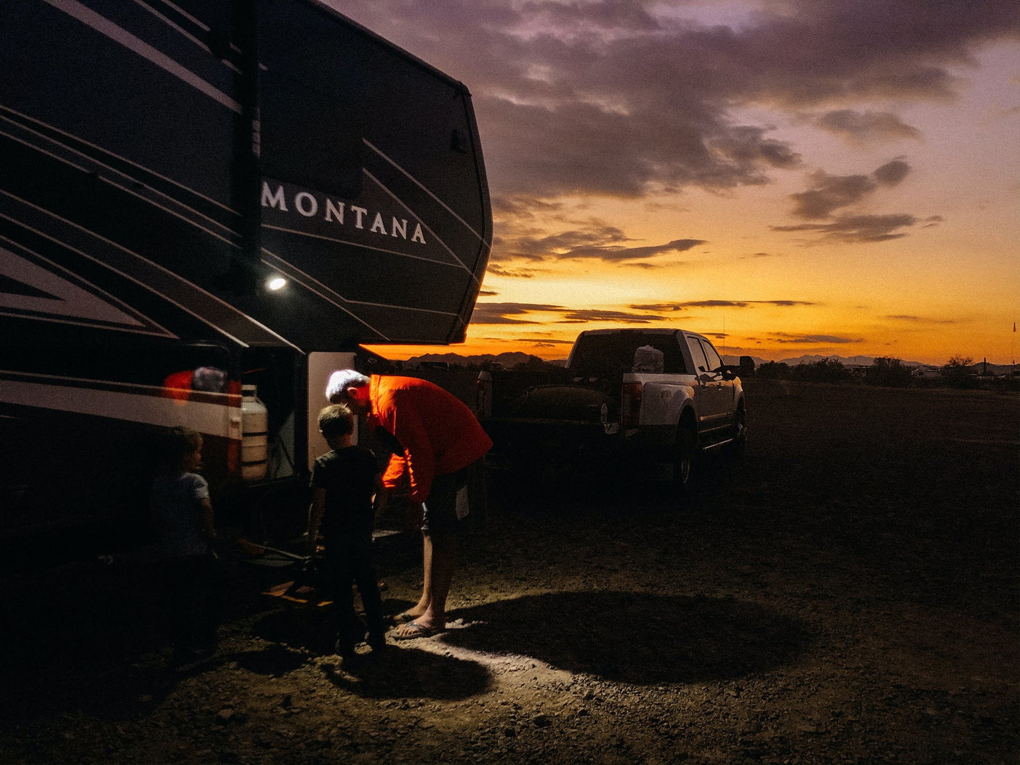 A father and son near the LP tank of their fifth wheel at sunset