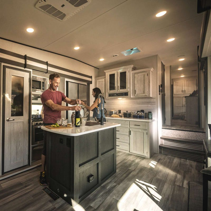 Couple making margaritas inside of a 2021 Sprinter fifth wheel.