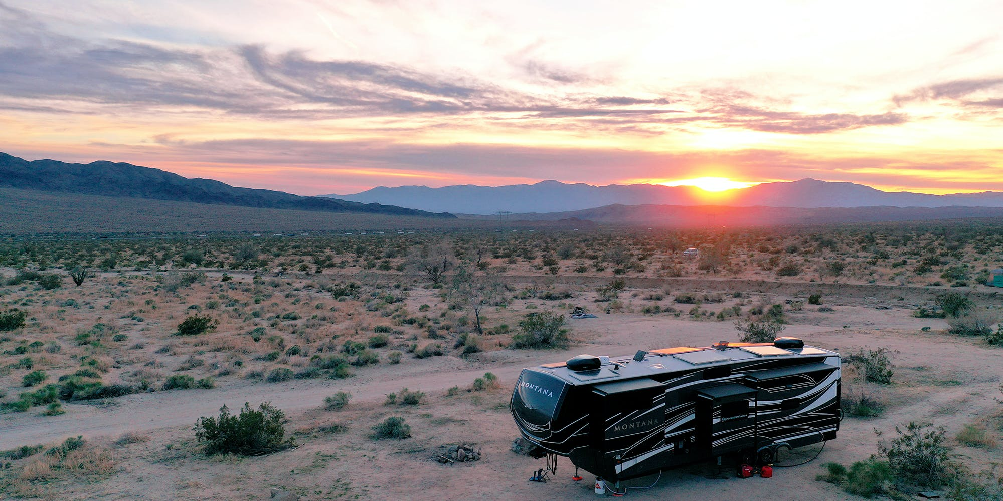 A fifth wheel parked in the desert with a beautiful orange and pink sunset in the background.