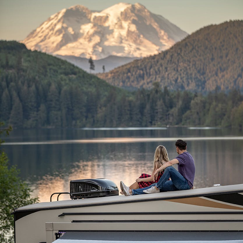 Couple sits atop a fifth wheel looking out at a mountain and lake