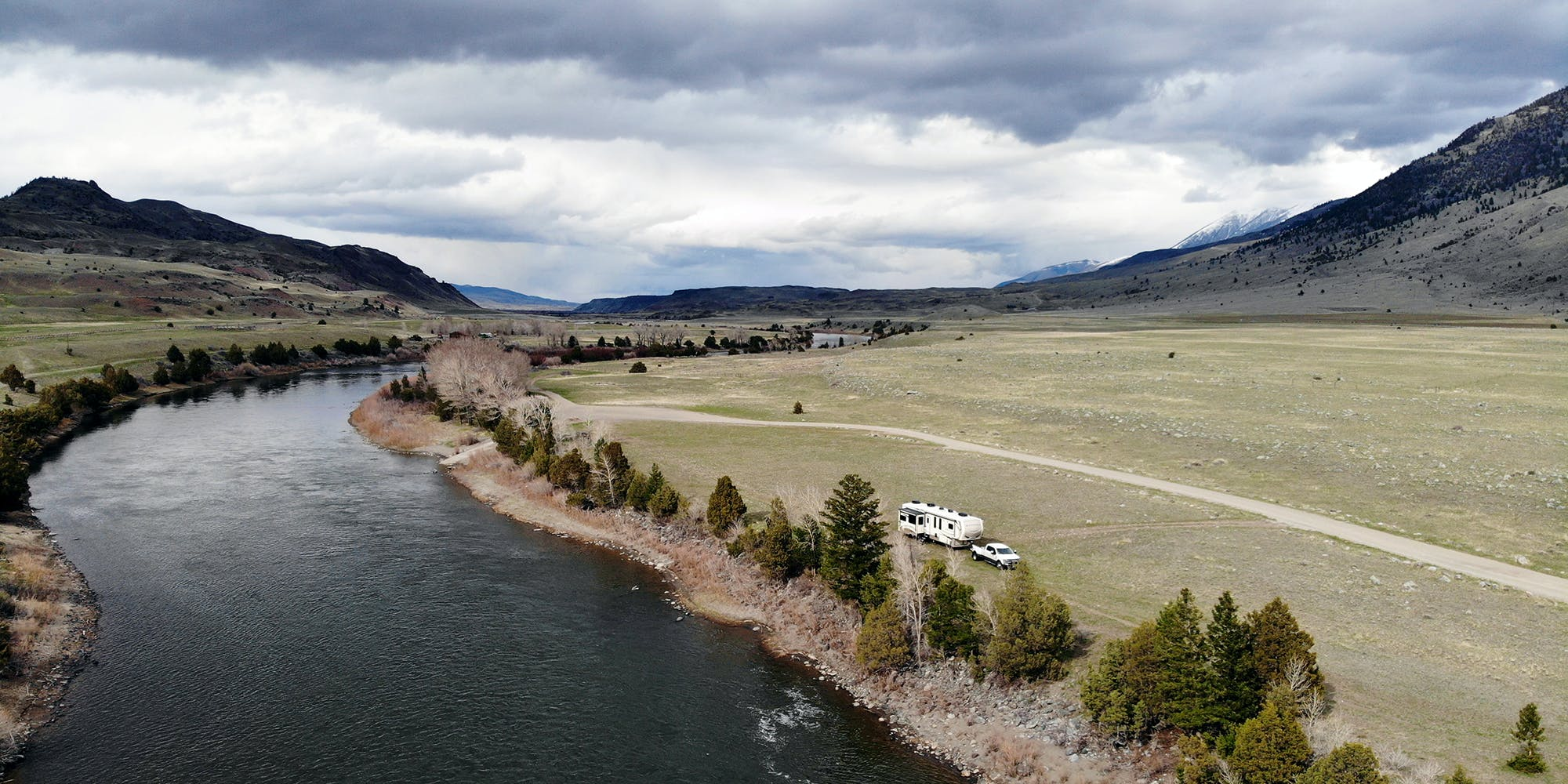 A fifth wheel parked alongside a river near Yellowstone National Park