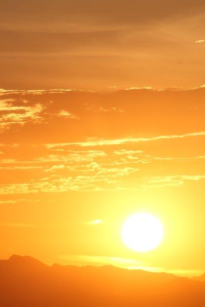 Sun setting behind mountains creating a bright orange sky.