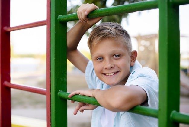мальчик блондин играет на улице