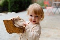 Barn i beige kofta som bär en bit ved
