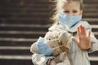 flicka i beige jacka med nalle och munskydd utomhus