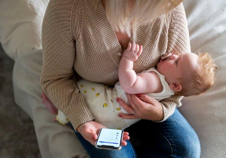 Mamma med bebis i knät