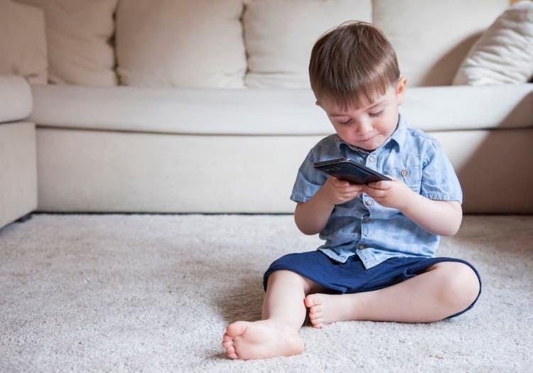 Pojke som sitter på golvet och tittar på en mobiltelefon