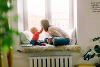 mamma och barn sitter i fönster