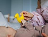 Bebis i säng som lekar med fågelleksak