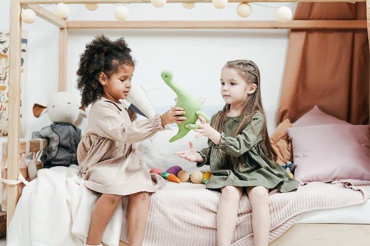 Två flickor som sitter i säng och leker