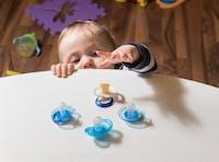 Barn som försöker nå nappar som ligger på ett bord