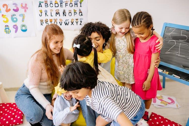 Barn och pedagoger kramas på förskolan