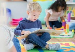 Pojke som läser en bok på förskolan