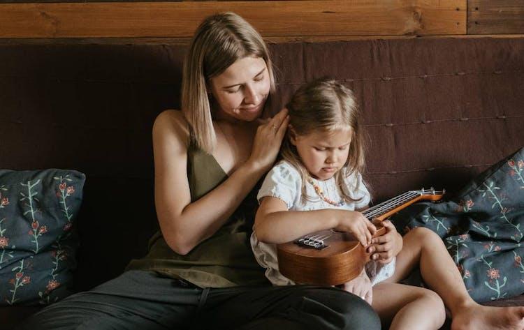 mamma och dotter som sitter i säng. Dottern har en gitarr