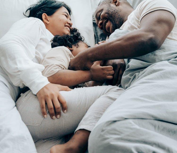 Två föräldrar i säng med ett barn emellan