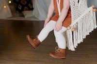 Barn som gungar i en repgunga med bruna läderskor