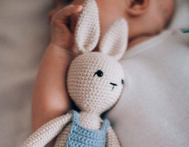 Lite bebis med uppstoppad kaningosedjur