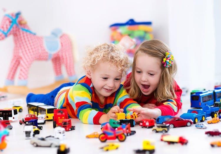 Pojke och flicka som leker med små bilar