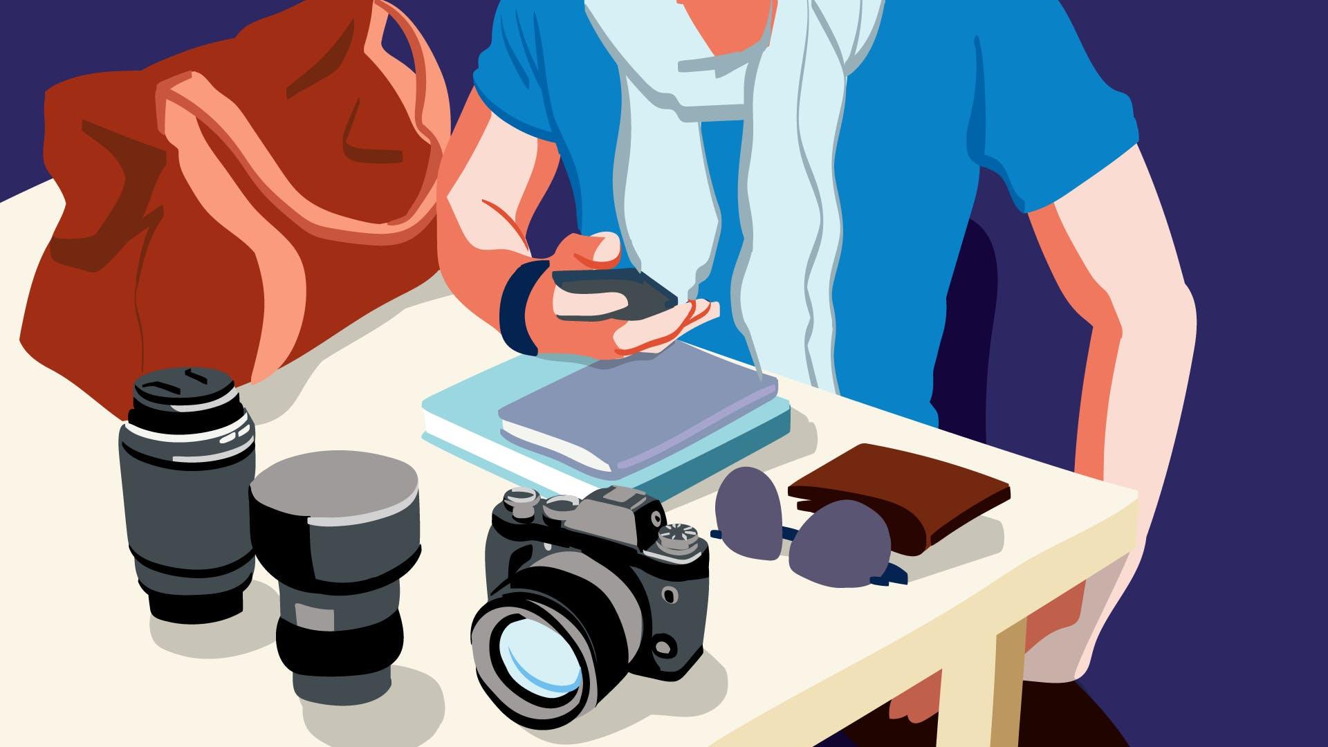 Fotograf vor seiner Kameraausrüstung an einem Tisch sitzend, prüft am Smartphone sinnvolle Tipps und Tricks für erfolgreiches Instagram Marketing.