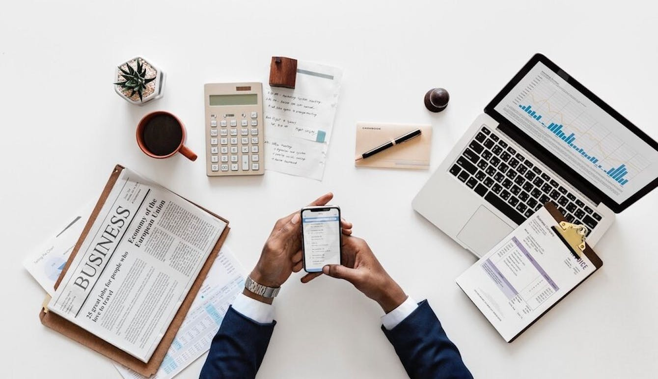 Image of person at desk doing bookkeeping and accounting with smartphone, laptop, calculator, pen, and paper