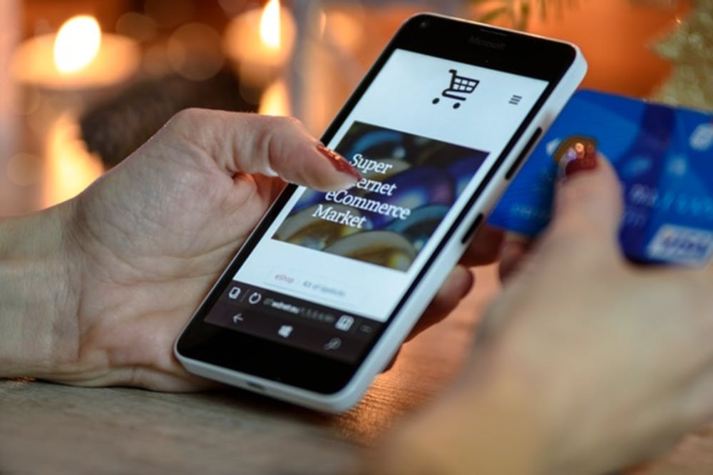 Hand holding a phone with ecommerce website