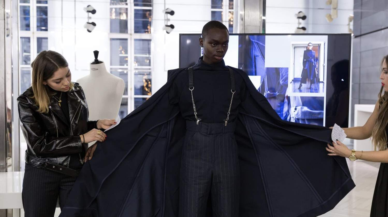 Decorative: Man being fitted into garment at a fashion show