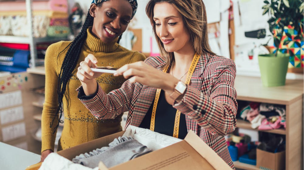 Decorative: Women using phone to photograph apparel in a shipping box