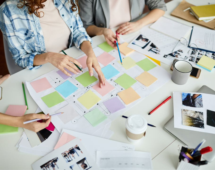 Decorative: Fashion professionals meeting at a workstation with post-its and papers