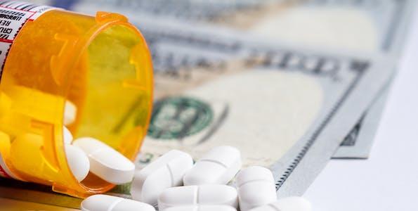 Prescription drugs falling out of a pill bottle onto one hundred dollar bills