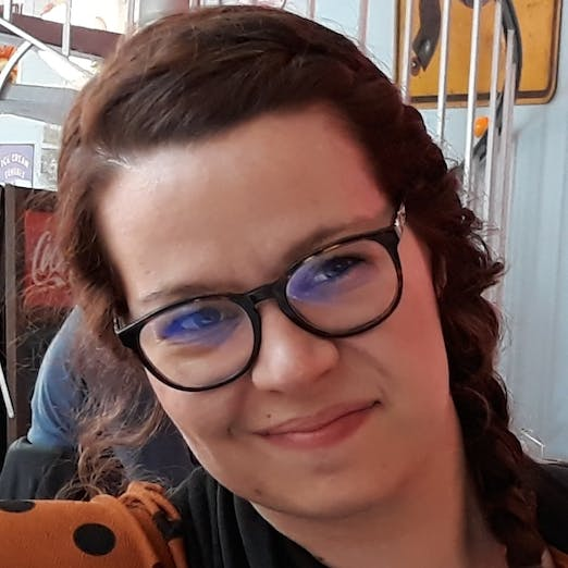 Photo of Aurore Geraud in eyeglasses, smiling with a phone near her face.