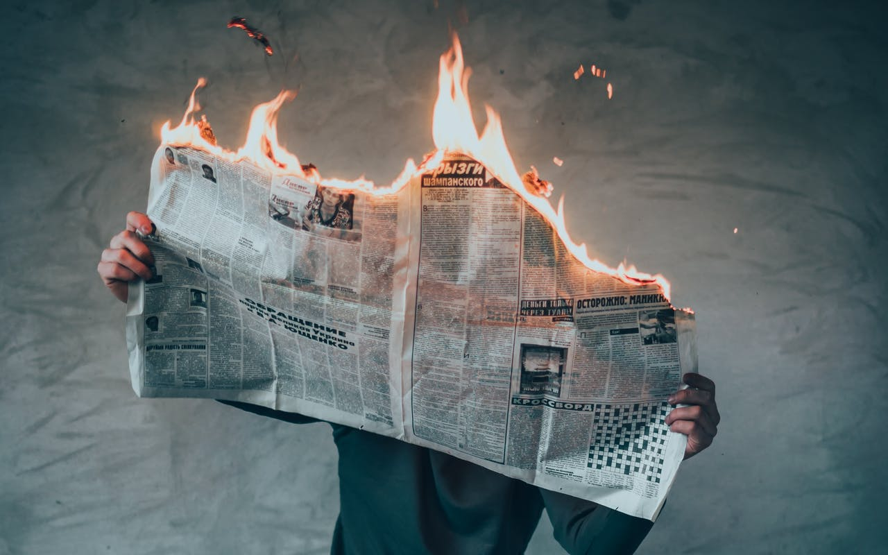 Man on a stool reading a newspaper that's on fire