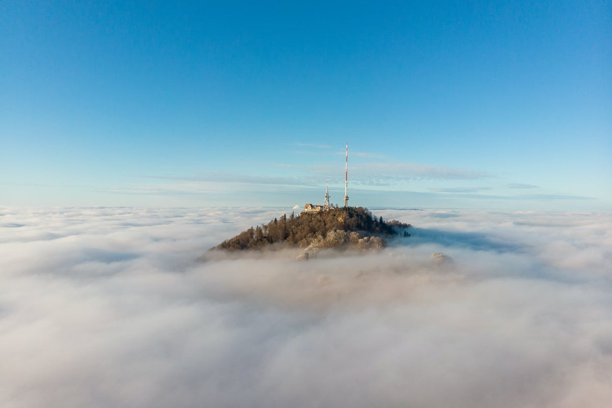 Mountain top with a phone mast poking above a cloud layer