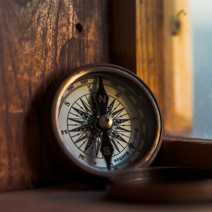 old fashioned brass compass on a wooden window ledge