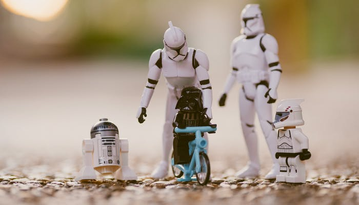toy stormtroopers teaching a lego Darth Vader to ride a bike