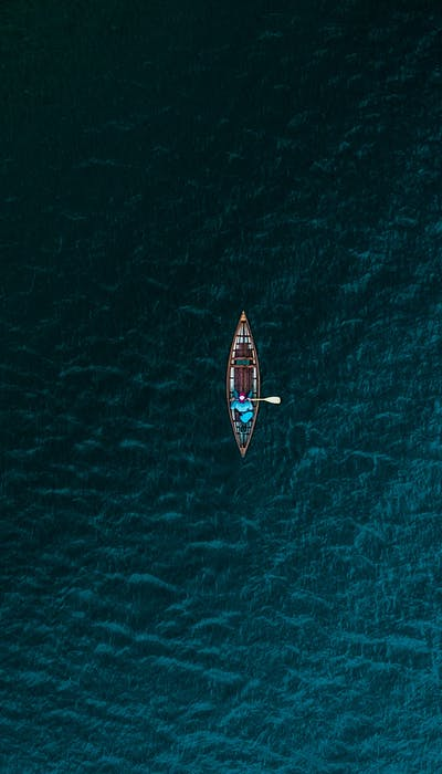 Man alone on a row boat in a blue lake