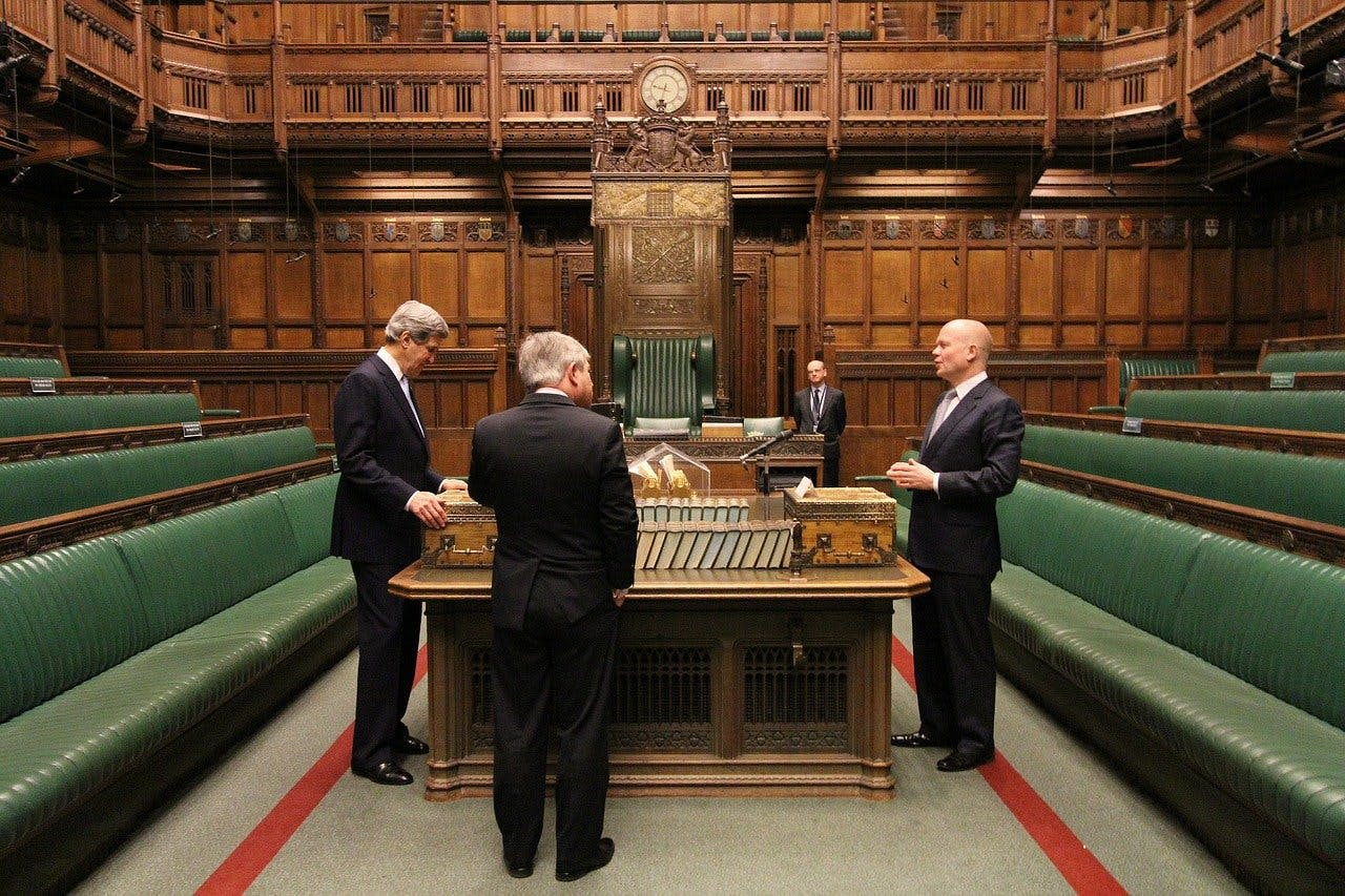 house of commons, green benches, nearly empty, MP's in suits