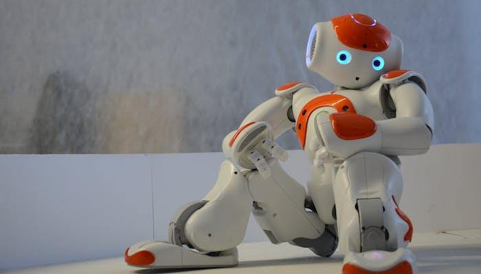 Toy robot sitting down shrugging