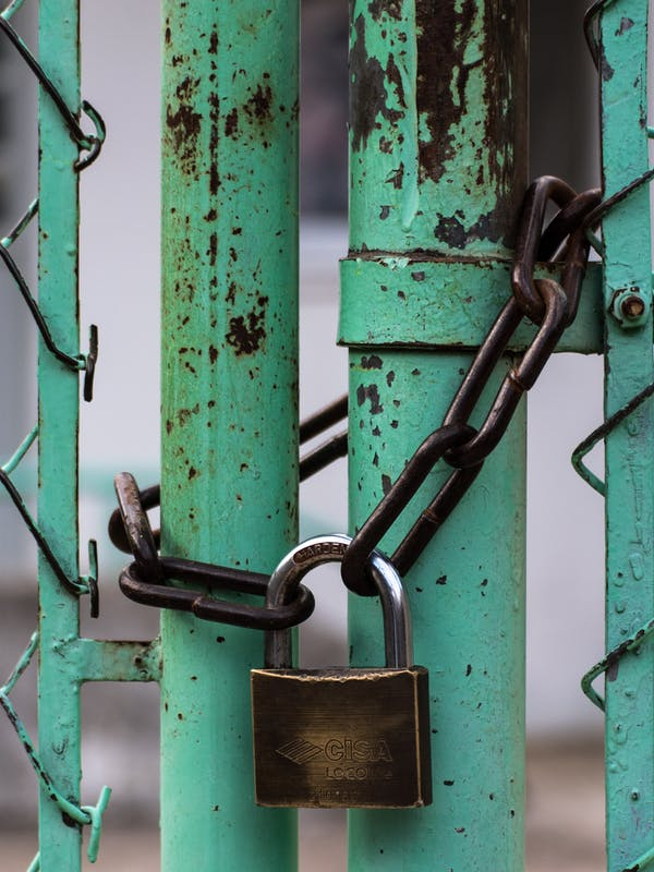 Padlocked green chainlink fence with a rusty padlock
