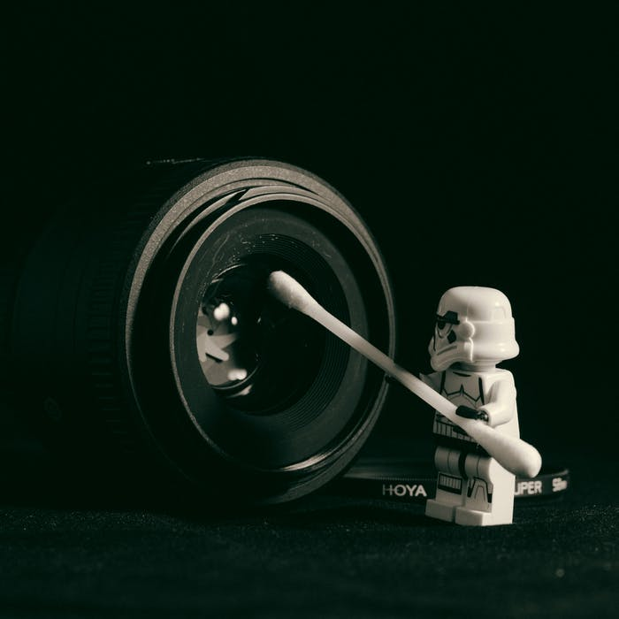 Lego stormtrooper cleaning a camera lens with a cotton bud