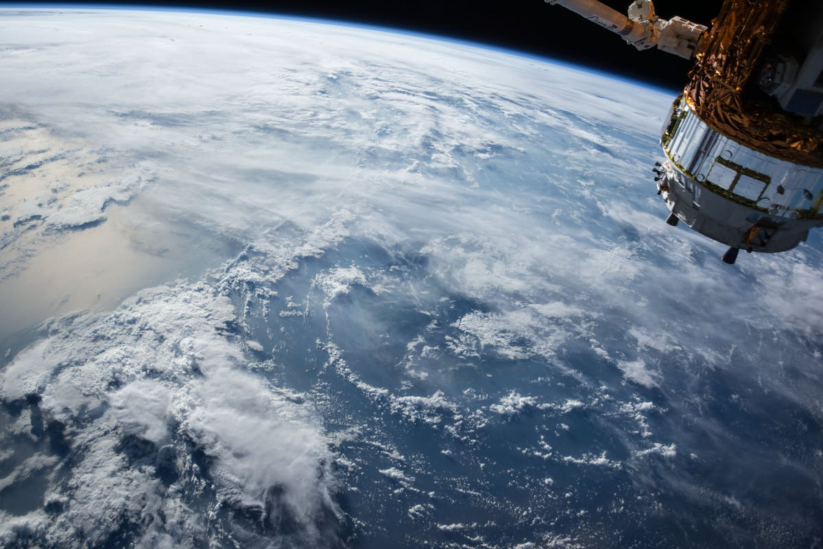 NASA satellite orbiting the earth with a view of the globe, clouds and sea in the background