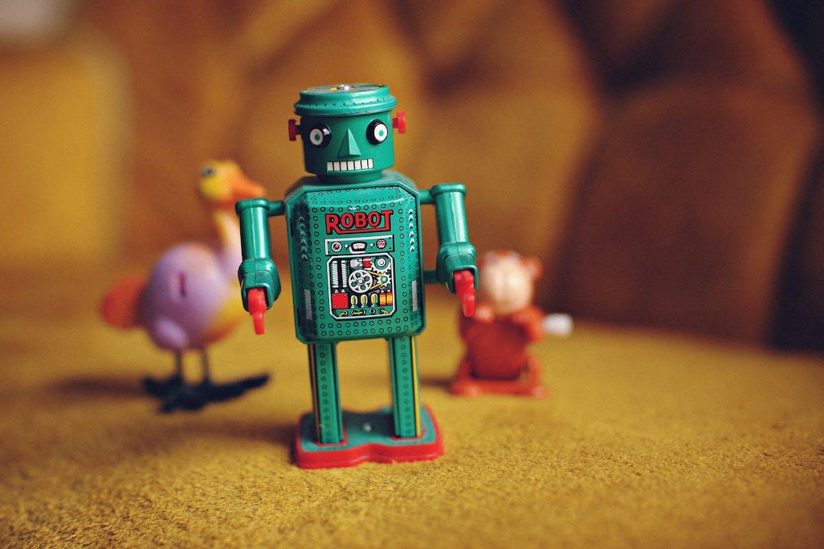 50's style green tin toy robot on a yellow carpet