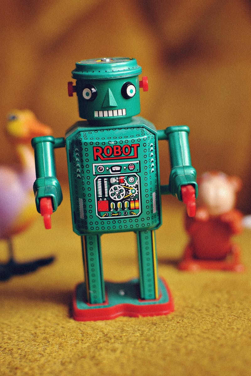 50's style green tin toy robot on a yellow carpet