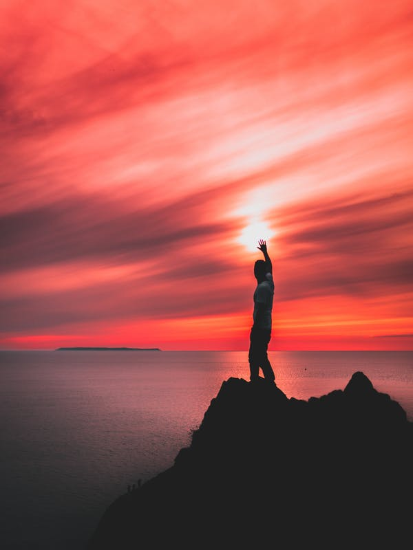 Red cloudy sky over the ocean with a man on a rock pretending to touch the sun