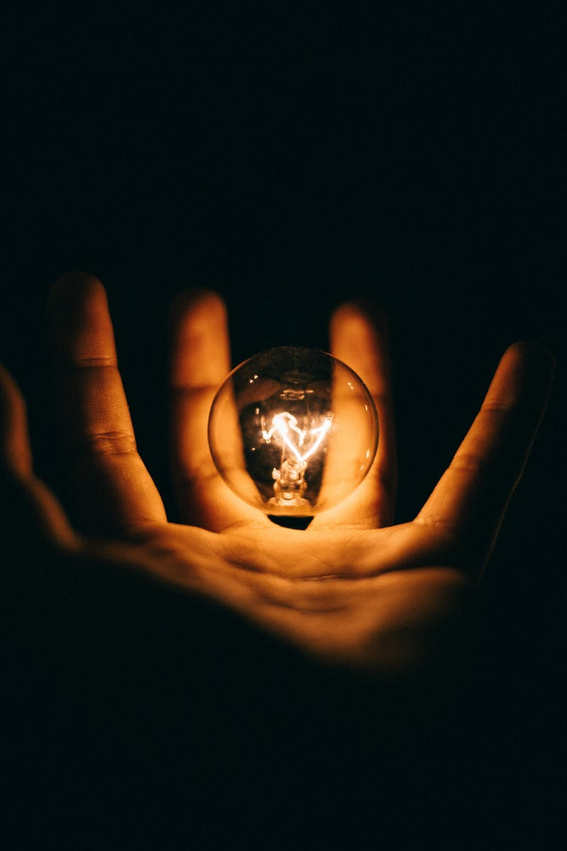 hand illuminated by a light bulb in a black background