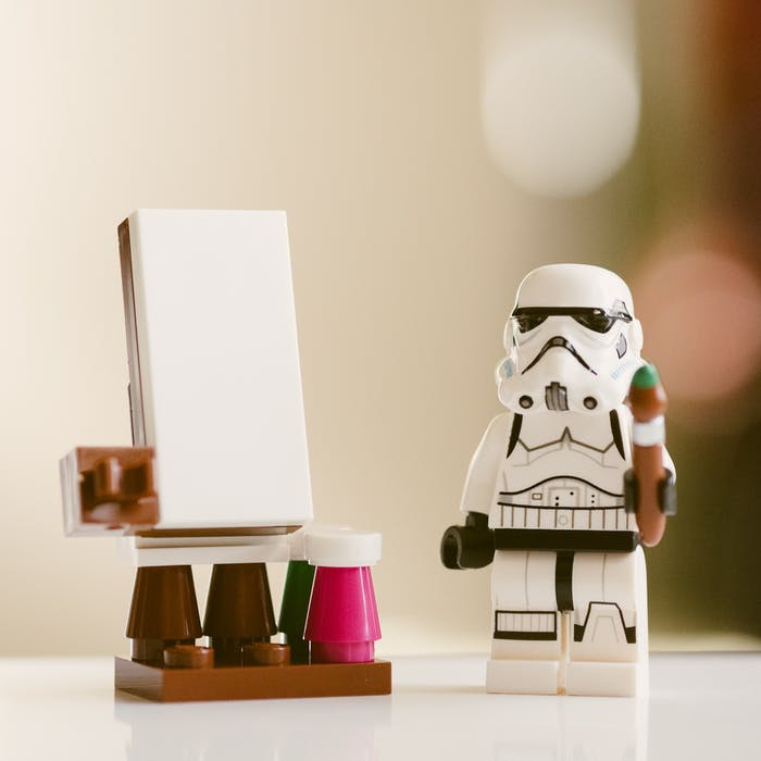 A lego storm trooper painting at an easel