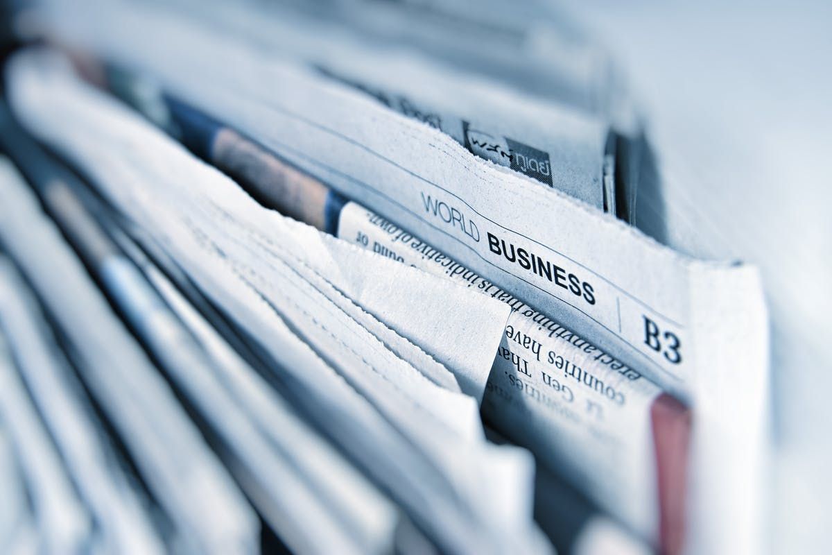 Stack Of Newspapers with world business in focus