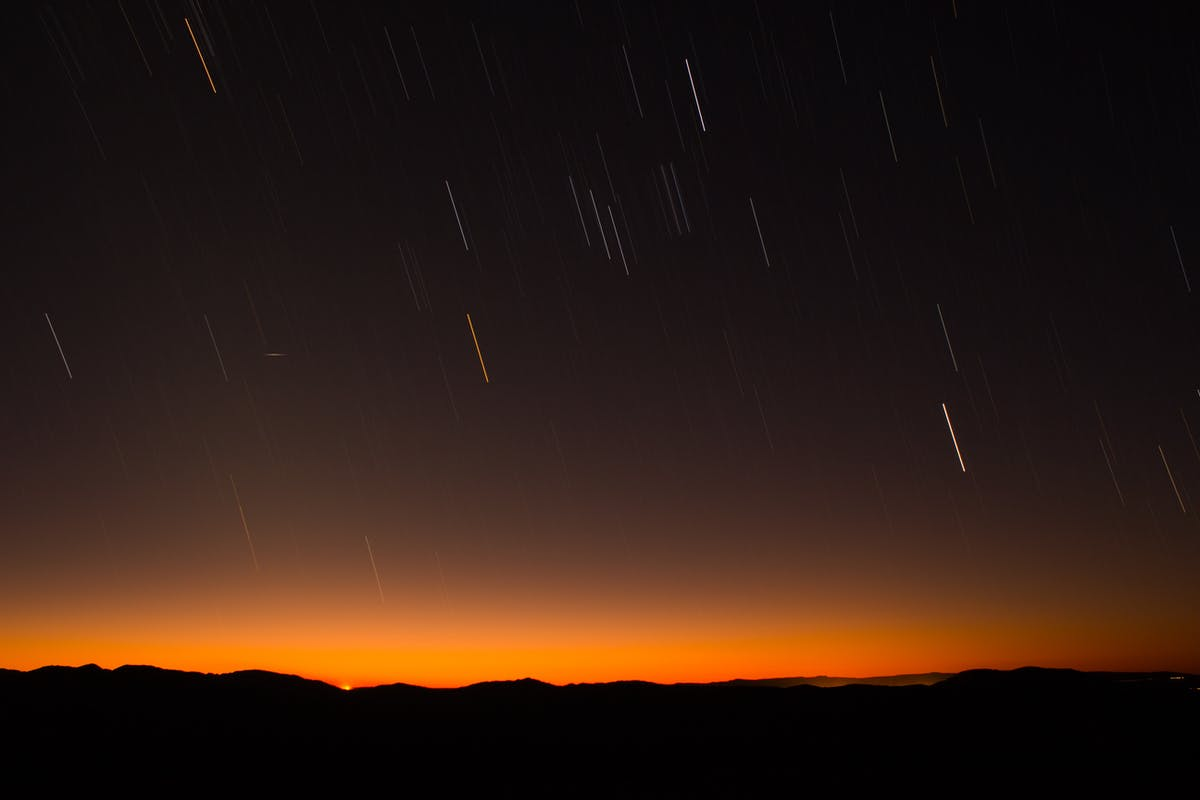 Shooting stars over a hill with an orange sunset silhouetting the hills